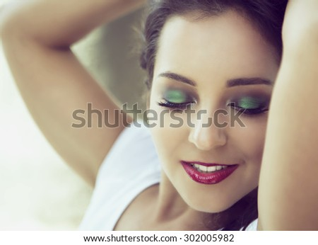 young woman with green eyeshadow and bright makeup, closeup - stock photo