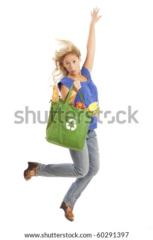 Young woman with green recycled grocery bag of healthy food and vegetables