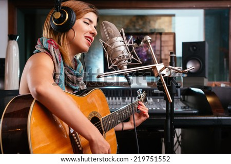 Young woman with guitar recording a song in the studio - stock photo