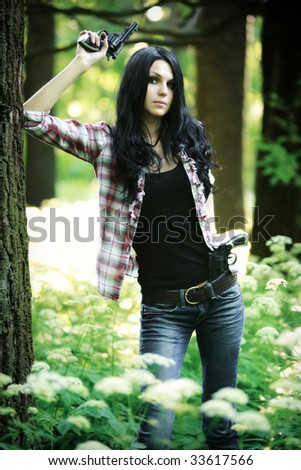 Young woman with guns in a forest. - stock photo