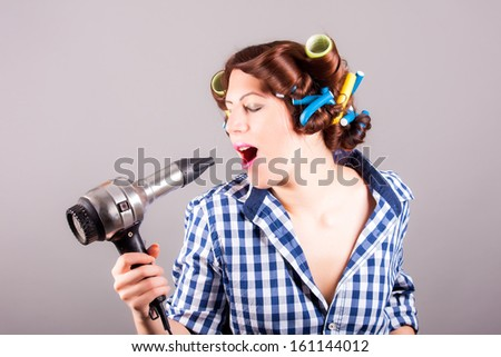 young woman with hair blower - stock photo