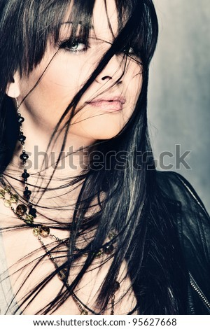 young woman with hair over face, studio shot - stock photo