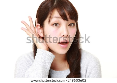 young woman with hand behind ear listening closely - stock photo