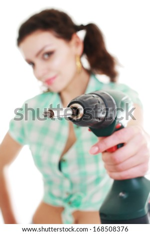 young woman with hand drill on a white background focus on the end of the drill and woman is out of focus Shallow depth