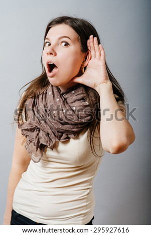 Young woman with hand near ear listen. On a gray background. - stock photo