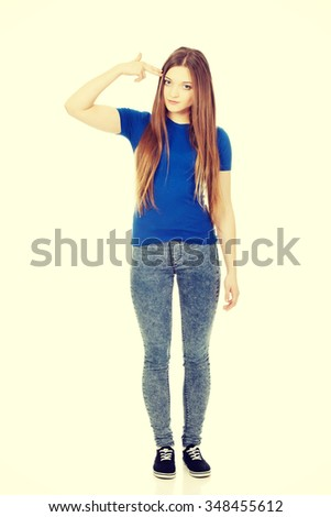 Young woman with hand to head in the shape of gun. - stock photo