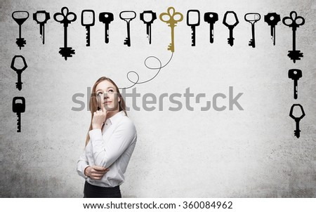 Young woman with hand to the chin looking up in search of the right solution which are presented as keys around her. Concrete background. Concept of finding a solution. - stock photo