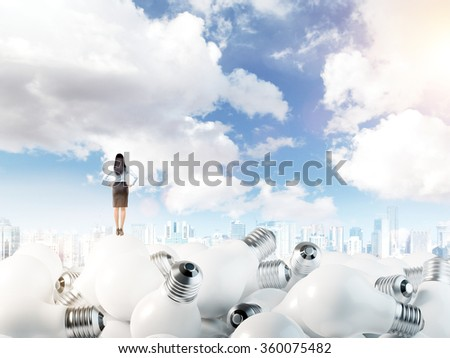 Young woman with hands on hips standing on huge scattered bulbs. Blue sky at the background. Back view. Concept of new ideas.