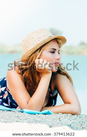 Young woman with hat on the beach