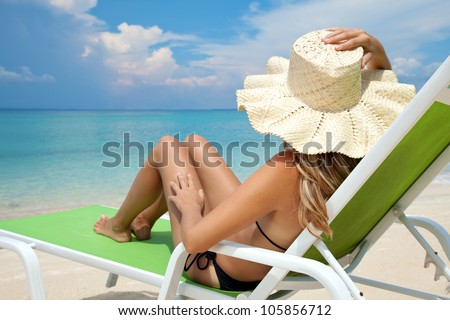 Young woman with hat relaxing on a deck chair - stock photo