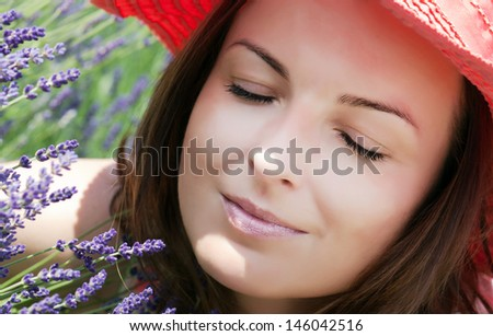 Young woman with hat sniffs purple lavender flowers.