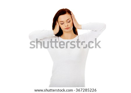 Young woman with headache holding her hand to the head - stock photo