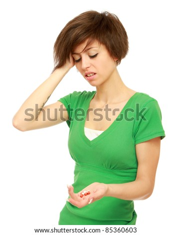 Young woman with headache looking at pills isolated - stock photo