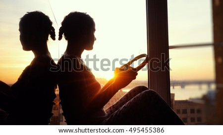 Young woman with headphones at city sunset background.