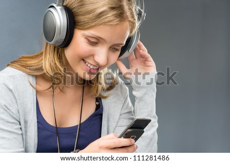 Young woman with headphones checking mobile phone looking message smiling - stock photo