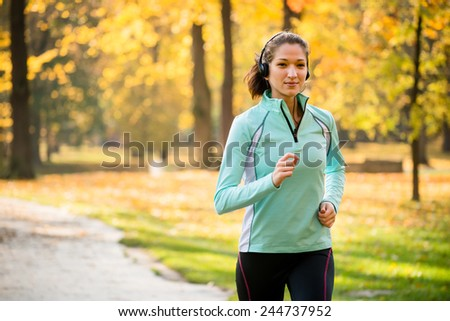 Young woman with headphones  jogging in fall nature and listening music - stock photo