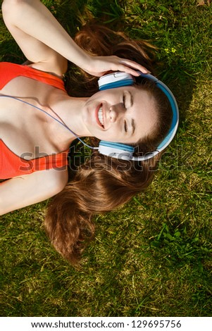 Young woman with headphones on green grass in the park - stock photo
