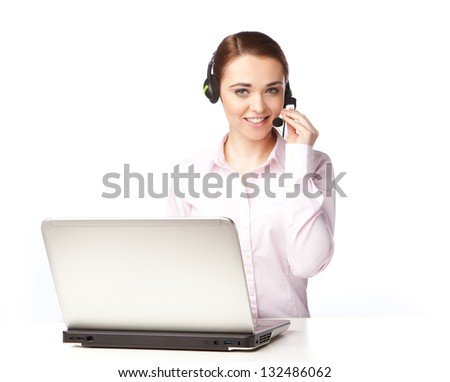 Young woman with headphones sitting at a laptop, smiling and looking at you, on the white background.