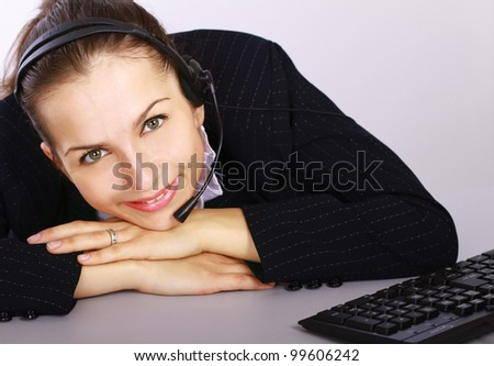 Young woman with headset lying on the table isolated on grey background - stock photo