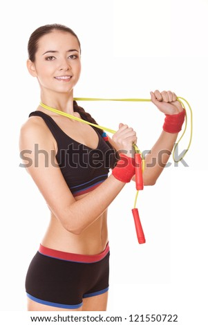 young woman with healthy sporty figure holding skipping rope - stock photo