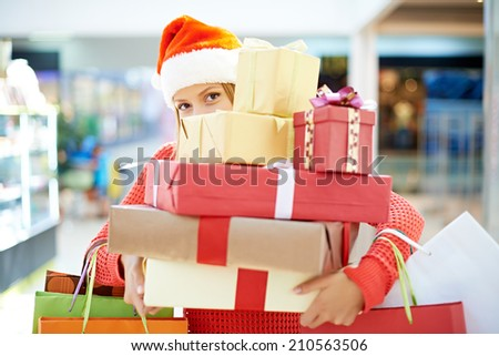 Young woman with heap of Christmas presents - stock photo