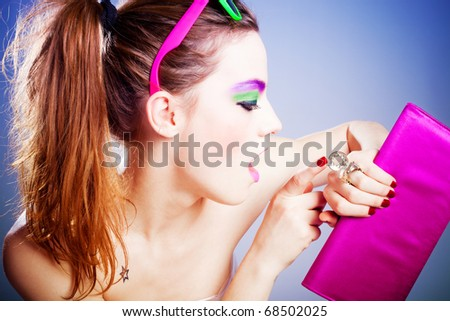 young woman with heavy make up looking at watch  in the form of ring, studio shot - stock photo
