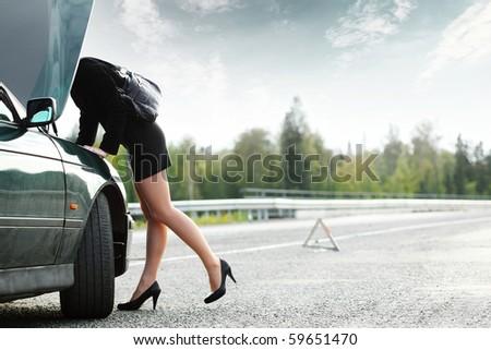 Young woman with heels repairing her broken car - stock photo