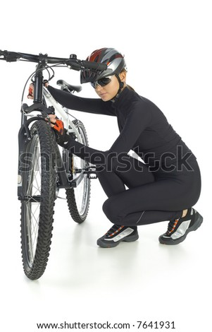 Young woman with helmet and sunglasses. Squatting next to mountain bike. White background. Whole body, front view - stock photo
