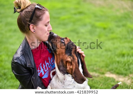 Young woman with her affectionate one year old Basset hound (Canis lupus familiaris) in the yard of a hobby farm.   Girl loves her dog, wet kisses from her patchy and multi toned Basset hound. - stock photo