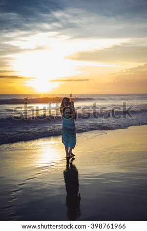 young woman with her baby on the beach during sunset . Mother with her baby on the beach watching the sunset.
