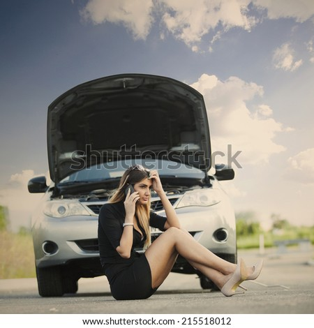 young woman with her broken car - stock photo