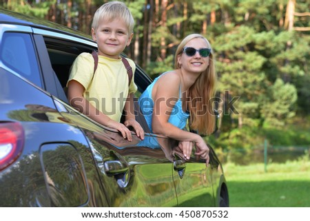 young woman  with her children sit in  modern car