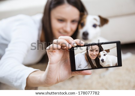 Young woman with her dog taking selfportrait - stock photo