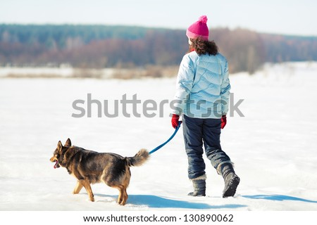 Young woman with her dog walking on the snowy field - stock photo