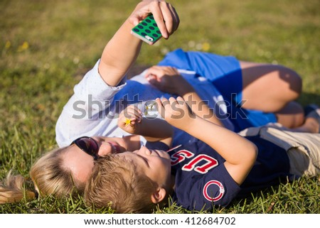 Young woman with her kid boy lying on the grass in the park  and enjoying sunny summer day. Mother with child taking selfie with smartphone. Family making picture with telephone. - stock photo