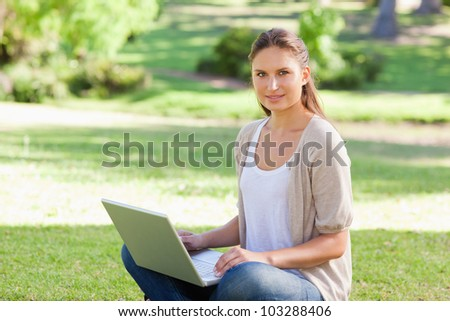 Young woman with her laptop sitting on the grass