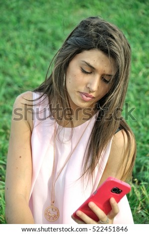 Young woman with her smartphone in field