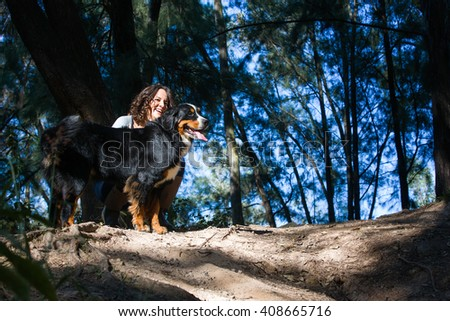 Young woman with her swiss Bernese mountain dog in a clearing in the forest - stock photo
