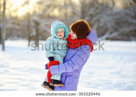 Young woman with her toddler boy at the winter park  - stock photo