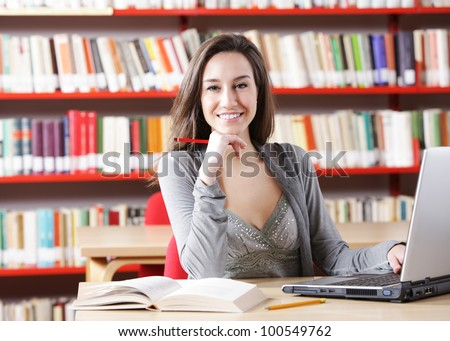Young woman with his laptop computer at the library. - stock photo
