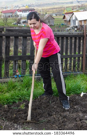 Young woman with hoe digging on ground
