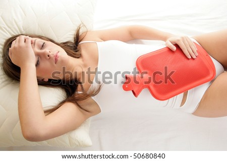 Young woman with hot water bottle on stomach lying on bed - stock photo