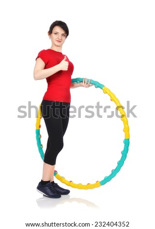 Young woman with hula hoop showing thumb up - stock photo