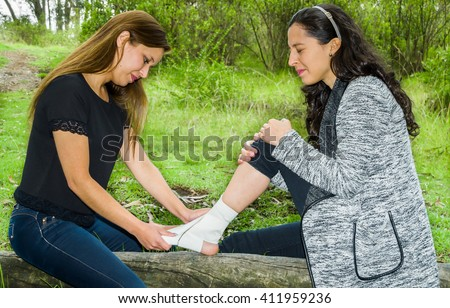 Young woman with injured ankle sitting on fallen tree and getting bandage compression wrap from female friend - stock photo