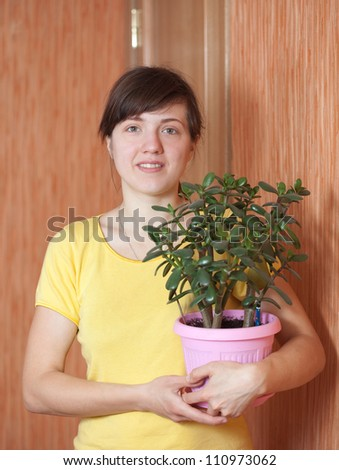 Young woman with jade tree in flowering pot  at her home - stock photo
