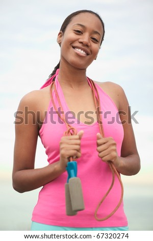 Young woman with jump rope on shoulders - stock photo