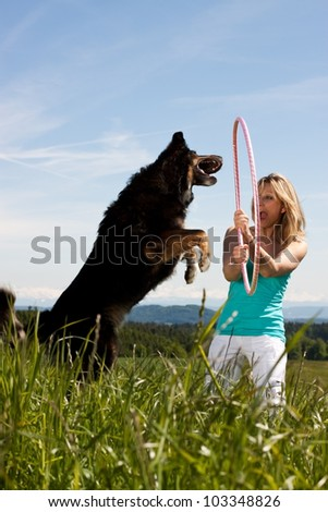Young woman with  jumping dog on a lawn. In the background, mountains and forests - stock photo