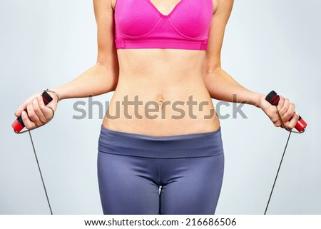 Young woman with jumping rope in her hand. - stock photo
