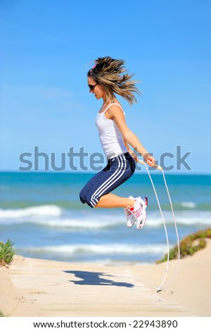 young woman with jumping rope on the beach