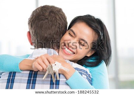Young woman with keys in hand embracing her husband - stock photo